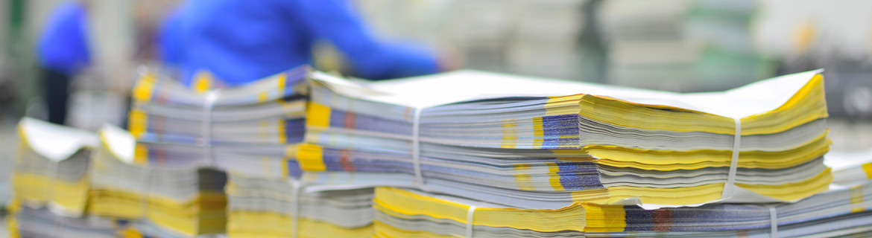 bilde viser en stabel med papir tatt ut fra trykkpressen