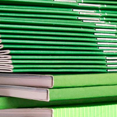Bilde viser eksempel på en grønn brosjyre både som limbundet, og som stiftet