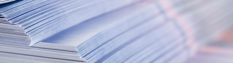 Bilde viser en haug med foldere som akkurat er ferdig i trykkeriet.